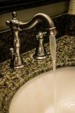 Rubinetto della stanza da bagno con acqua corrente Fotografia Stock