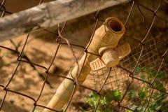 Rubinetto di plastica del tubo sporco del PVC del primo piano - Rusty Old Wire Fence - ciarpame abbandonato - soleggiato immagine stock