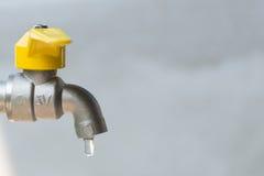 Rubinetto giallo d'argento colante con goccia di acqua Fotografie Stock Libere da Diritti