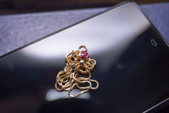 Rubinowa i złocista kolia na czarnej telefon komórkowy powierzchni fotografia royalty free