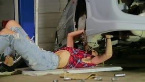 Rubio atractivo en reparaciones de un garaje un coche almacen de video