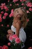 Rubio atractivo en rosas rosadas Imágenes de archivo libres de regalías