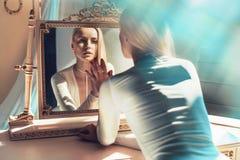 Rubio elegante mirando su reflexión de espejo fotografía de archivo