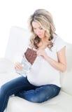 Rubio embarazada de Yound teniendo una mordedura de la barra de chocolate Fotos de archivo