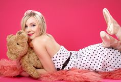 Rubio encantador con el oso de peluche sobre color de rosa Imágenes de archivo libres de regalías
