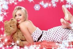 Rubio encantador con el oso de peluche sobre color de rosa Fotos de archivo