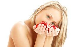 Rubio encantador en balneario con los pétalos color de rosa rojos y blancos Fotografía de archivo