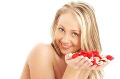 Rubio encantador en balneario con los pétalos color de rosa rojos y blancos Imágenes de archivo libres de regalías