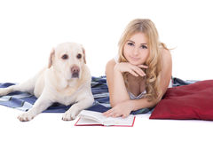 Rubio hermoso joven en los pijamas que mienten con el aislante del libro y del perro Imagenes de archivo