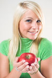 Rubio joven apto ofreciendo una manzana roja. Imágenes de archivo libres de regalías