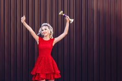 Rubio joven atractivo en un vestido rojo sostiene la taza de campeón y es muy feliz imágenes de archivo libres de regalías