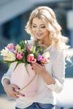 Rubio joven hermoso con el pelo ondulado al aire libre con un ramo grande de flores en una calle brillante en la ciudad imagen de archivo libre de regalías