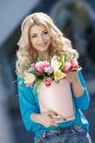 Rubio joven hermoso con el pelo ondulado al aire libre con un ramo grande de flores en una calle brillante en la ciudad fotos de archivo libres de regalías