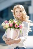Rubio joven hermoso con el pelo ondulado al aire libre con un ramo grande de flores en una calle brillante en la ciudad imágenes de archivo libres de regalías