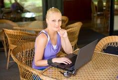 Rubio joven hermoso divirtiéndose con la computadora portátil. Imagen de archivo