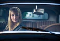 Rubio joven hermoso en un coche de la vendimia. Fotos de archivo