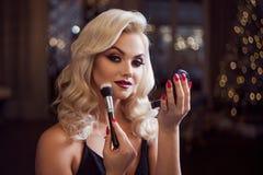 Rubio joven hermoso hace un maquillaje brillante del día de fiesta Maquillaje atractivo Una mujer joven atractiva utiliza el polv fotos de archivo