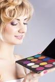 Rubio joven hermoso, sosteniendo la gama de colores de la sombra de ojo Imagen de archivo