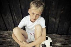 Rubio joven y el azul observaron al jugador de fútbol en blanco Imagen de archivo libre de regalías