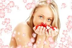 Rubio precioso con los pétalos color de rosa rojos y blancos y Foto de archivo libre de regalías