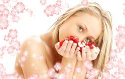 Rubio precioso en balneario con los pétalos rojos y blancos y Imagen de archivo
