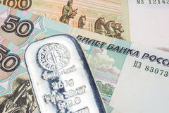 Ruble backed by precious metals. Silver brick laying on ruble banknotes Royalty Free Stock Photography