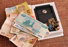 Ruble, hryvnia, jewelry and mini-safe on a homogeneous backgroun. Ruble, hryvnia, jewelry lying on miniature metal safe. Uniform background sackcloth Royalty Free Stock Photos