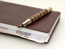 Money inside the diary, and pen Royalty Free Stock Photography