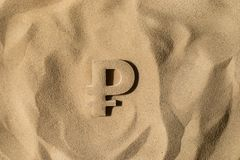 Ruble Symbol Under the Sand. Russian Ruble Symbol or Sign Covered with Sand in the Sun after Crisis stock image