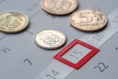 Rubles coins lying on the calendar. Highlighted in figure 15 Stock Image