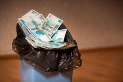 Rubles in trash bin. Trash bin filled with Russian banknotes stock photo