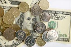 Rubli russe di monete sulle banconote dei dollari Immagini Stock