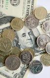 Rubli russe di monete sulle banconote dei dollari Fotografia Stock