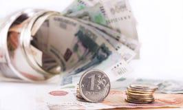 Rublo en el fondo del tarro con el dinero Fotografía de archivo