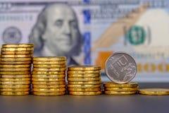 Rublo rusa en la moneda que rueda abajo en fondo del billete de banco de 100 dólares imagen de archivo libre de regalías