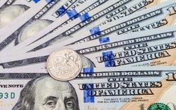 Rublos rusas de monedas sobre billetes de banco de los dólares Foto de archivo libre de regalías