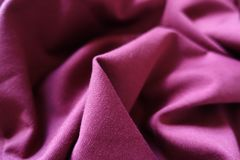 Ruby colored stockinet fabric in soft folds. Ruby colored stockinette fabric in soft folds Royalty Free Stock Photo