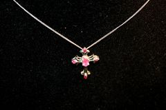 Ruby. Cross necklace on a black background Royalty Free Stock Photography