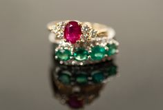 Ruby and emerald rings in diamond settings Royalty Free Stock Photo
