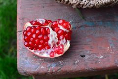 Ruby grains of pomegranate on chair in garden Stock Photography