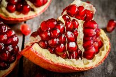 Ruby juicy pomegranate grains closeup on a table Stock Photo