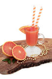 Ruby Red Grapefruit Juice Drink. With fresh fruit, striped straws and gold bead decorations on an olive wood board over white background. High in vitamins stock photography