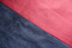 Ruby red and dark blue artificial suede sewn together diagonally. Ruby red and navy blue artificial suede sewn together diagonally Royalty Free Stock Photo