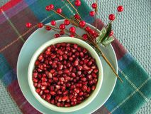 Bowl of fresh jewel-like pomegranate seeds. Ruby red pomegranate seeds in festive Christmas holidays table setting with plaid table runner and aqua blue rattan stock photography