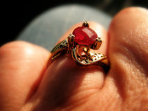 Ruby ring on finger. Close-up of Mothers Day ring with a ruby in center and word mom inscribed in ring royalty free stock photos