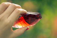 Ruby rock. Two fingers holding red piece of glass Royalty Free Stock Image