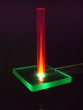 Ruby rod under laser beam. A rod of artificial ruby is lit up from bottom with a green laser beam royalty free stock images
