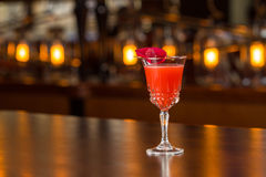 Ruby Rose cocktail. A cocktail on wooden bar with lights on background Royalty Free Stock Images
