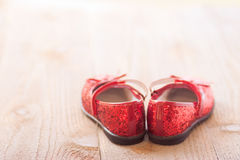 Ruby slippers. A pair of red sparkly little girls mary jane style shoes with glitter and bows, positioned with the heels together Stock Photos
