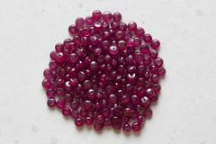 Ruby stones lie on a white table, a white background. Natural stones ruby, ruby beads. Pink ruby background.  stock photos